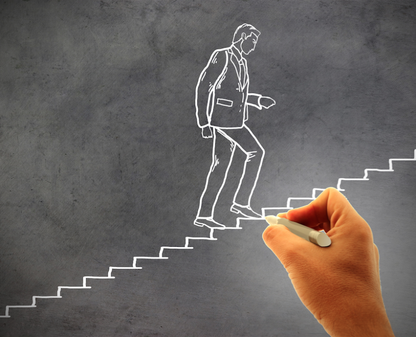 Chalk drawing of a businessman climbing a staircase